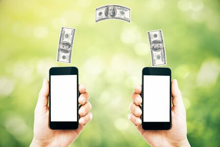 money online: Online money transfer concept with two male hands holding smart phones with blank white screens and dollar bills above on abstract green background. Mock up, 3D Rendering