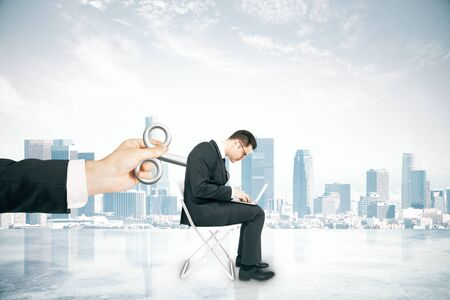 activating: Hand activating businessman with a wind-up key on his back on foggy city background. Concept of control