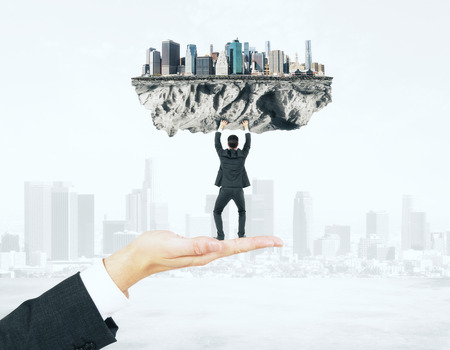 upholding: Businessman miniature standing on hand and upholding abstract city on foggy background