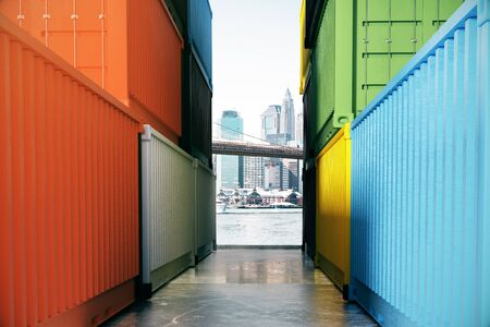 between: Concrete path with city view between colorful cargo containers. 3D Rendering