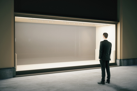 Businessman looking at empty showcase at night. Mock up, 3D Rendering 스톡 콘텐츠