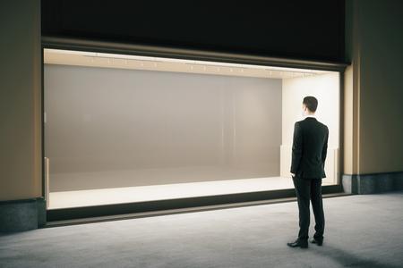 Businessman looking at empty showcase at night. Mock up, 3D Rendering Foto de archivo