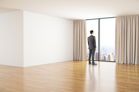 looking at view: Spacious clean room interior with wooden floor, concrete walls and businessman looking out of window with curtains and city view. Mock up, 3D Rendering