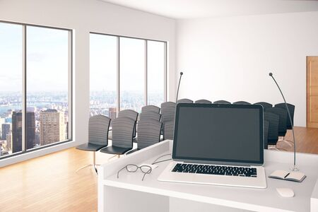 lecture hall: Conference hall interior with blank laptop on stand with microphones, glasses and windows with city view. Mock up, 3D Rendering Stock Photo