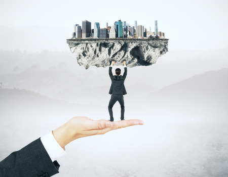 upholding: Businessman miniature standing on hand and upholding abstract city on misty background