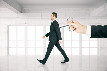 creative force: Hand activating walking businessman with a wind-up key on his back in white brick room. Concept of control