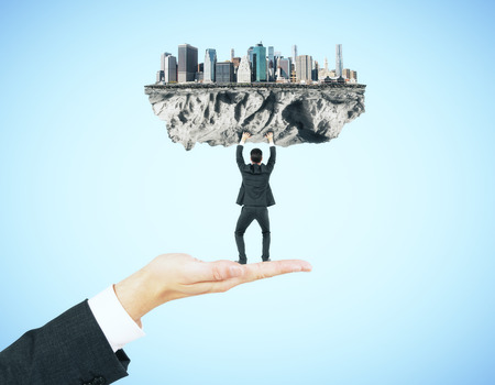 upholding: Businessman miniature standing on hand and upholding abstract city on blue background Stock Photo