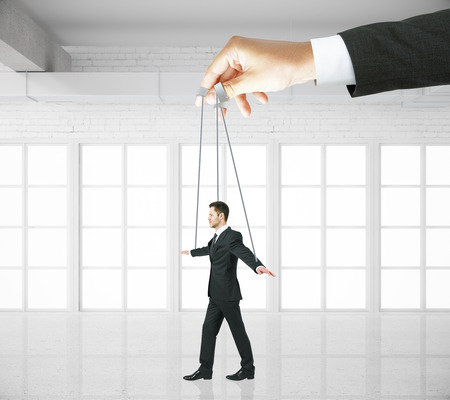 manipulating: Hand manipulating businessman puppet on ropes in white brick interior. Concept of control
