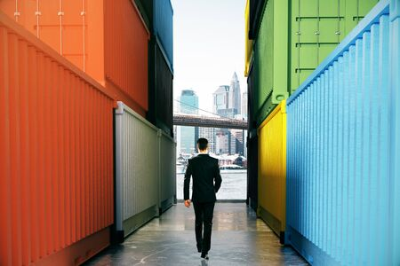 walking path: Businessman walking towards city on concrete path between cargo containers. Success concept, 3D Rendering Stock Photo