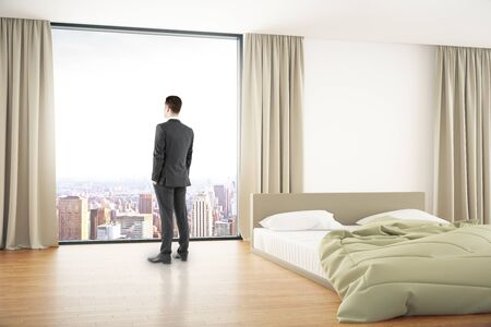 unmade: Thoughtful businessman looking out of window in bedroom inteior with unmade bed and curtains. 3D Rendering Stock Photo