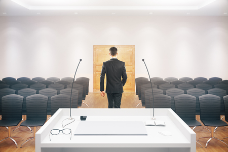 lecture hall: Businessman walking towards exit door in conference hall interior with speakers stand, rows of seats, wooden floor, concrete walls and ceiling. 3D Rendering Stock Photo