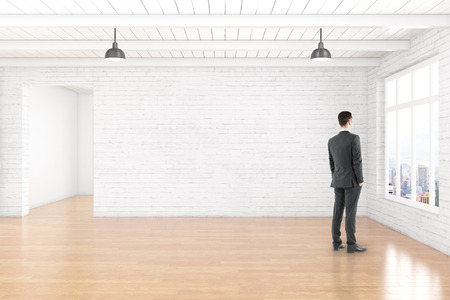 interior window: Thoughtful businessman in empty room interior with blank white brick wall, wooden floor, ceiling and window with city view. Mock up, 3D Rendering