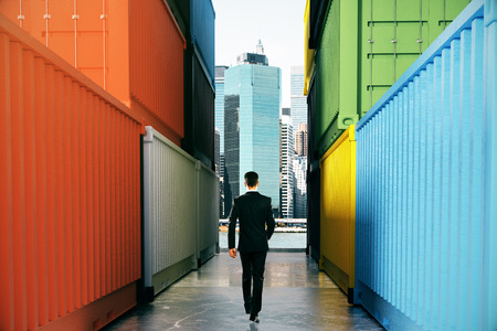 between: Businessperson walking towards city on concrete path between cargo containers. Success concept, 3D Rendering
