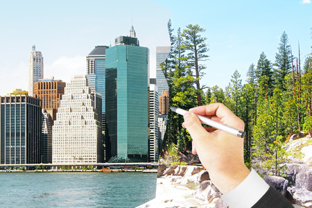 urbanization: Mans hand drawing modern city on landscape. Concept of urbanization Stock Photo