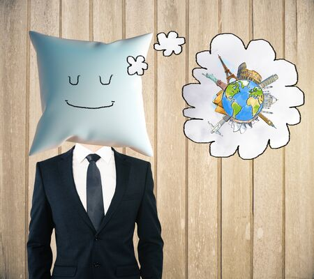 sleeping businessman: Sleeping businessman with smiley face on pillow instead of head dreaming about traveling on wooden background Stock Photo