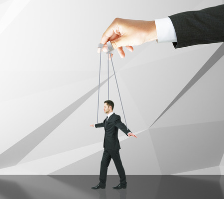 manipulating: Hand manipulating businessman puppet on ropes. Abstract concrete wall background. Concept of control