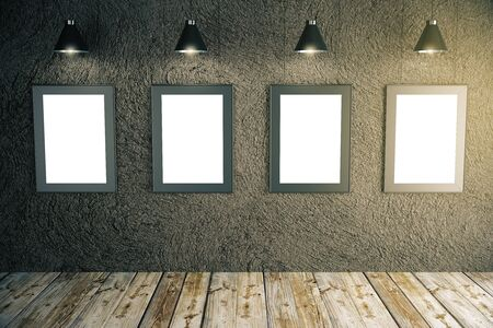 hang up: Front view of blank picture frames in room with dark concrete wall, wooden floor and ceiling lamps. Mock up, 3D Rendering Stock Photo