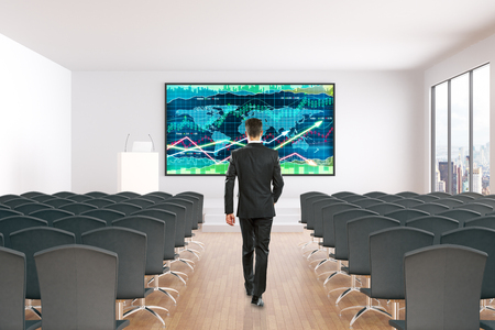 lecture hall: Businessman walking towards board with forex chart in conference hall interior with rows of seats, wooden floor, concrete walls and window with city view. Mock up, 3D Rendering
