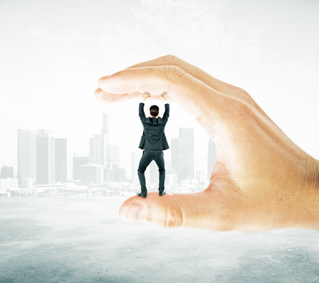 extortion: Businessman trapped between fingers of big hand on abstract city background. Pressure concept