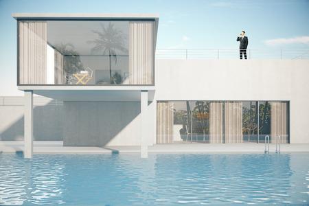 Zakenman praten over de telefoon op het dak van luxe huis exterieur met zwembad. 3D Rendering