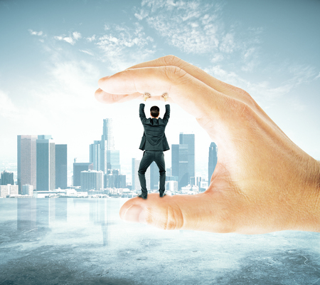 between: Businessman trapped between fingers of big hand on city background. Pressure concept