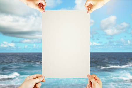 four hands: Four hands holding blank poster on sea and sky background. Mock up Stock Photo
