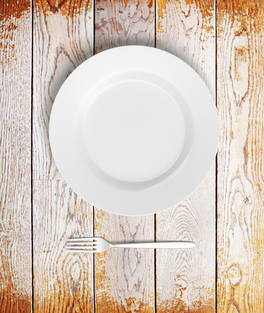 potluck: Top view of empty plate and fork on aged wooden table. Mock up, 3D Rendering
