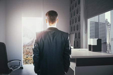 Businessperson standing in modern office interior with open door looking at landscape. Concept of choice between career development and traveling. 3D Rendering