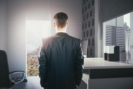 Hombre de negocios de pie en el interior de la oficina moderna con la puerta abierta mirando el paisaje. El concepto de elección entre el desarrollo de la carrera y viajar. Representación 3D