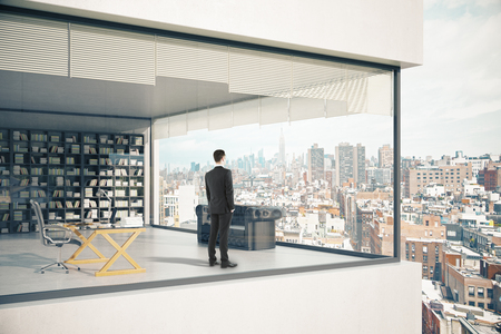See-through building exterior with panoramic windows, thoughtful businessman, workplace, couch and bookshelf on city background. 3D Rendering