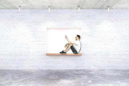 seating: Young man with smartphone on built-in-wall seating in white brick room. 3D Rendering