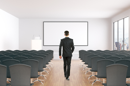 towards: Businessman walking towards blank whiteboard in conference hall interior with rows of seats, wooden floor, concrete walls and window with city view. 3D Rendering