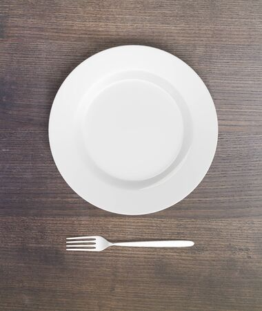 potluck: Top view of empty plate and fork on dark wooden table. Mock up, 3D Rendering