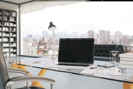 interior space: Closeup of creative office workplace with blank laptop, coffee cup, smartphone, hourglass and other items with bookshelf and window with city view in the background. Mock up, 3D Rendering