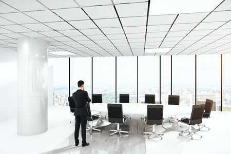 pensive: Pensive businessman in conference room interior with round table, chairs, concrete column and panoramic window with city view. 3D Rendering Stock Photo