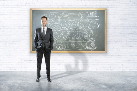 man studying: businessman standing in room and and drawing business concept on chalk board