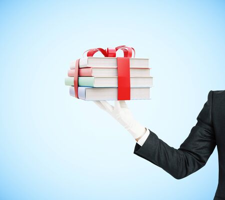 literary man: Businessman hand holding stack of colorful books tied up with a ribbon on blue background. 3D Rendering