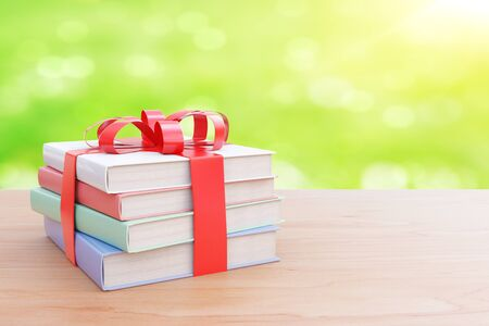 books on a wooden surface: Wooden surface with stack of colorful books tied up with a ribbon as a present on abstract green background. 3D Rendering