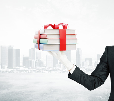 tied up: Businessman hand holding stack of colorful books tied up with a ribbon on city background. 3D Rendering Stock Photo