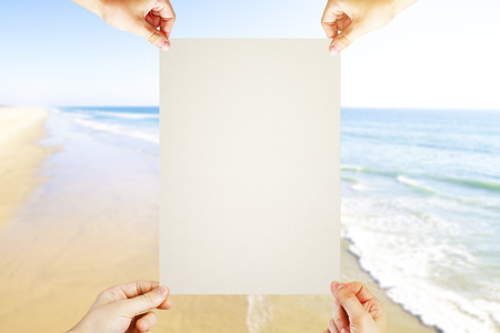 four hands: Four hands holding blank piece of paper on seaside background. Mock up