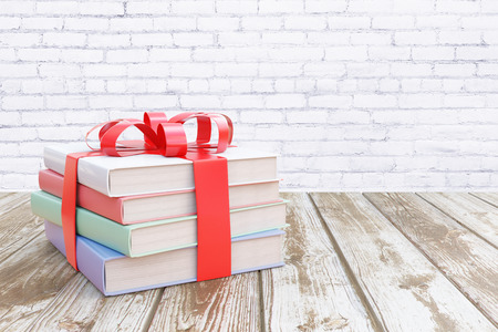 Aged wooden surface with stack of colorful books tied up with a ribbon as a present on white brick wall  background. 3D Rendering