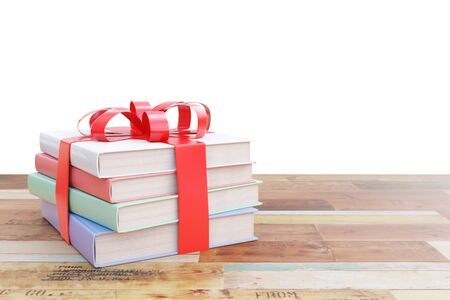 tied up: Aged wooden surface with stack of colorful books tied up with a ribbon as a present on white  background. 3D Rendering