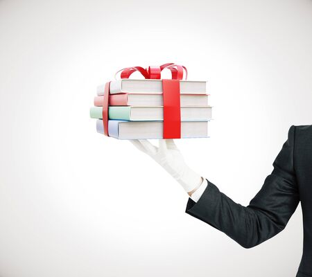 tied up: Businessman hand holding stack of colorful books tied up with a ribbon on grey background. 3D Rendering