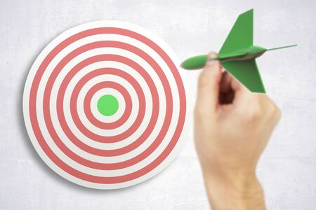 targeting: Targeting concept with businessman hand playing darts on light concrete wall background. 3D Rendering