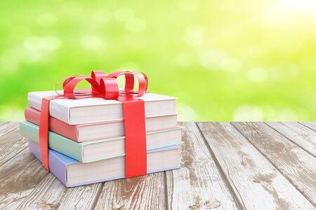 tied up: Aged wooden surface with stack of colorful books tied up with a ribbon as a present on abstract green background. 3D Rendering