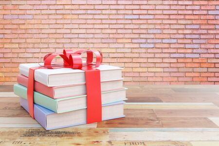 tied up: Aged wooden surface with stack of colorful books tied up with a ribbon as a present on red brick wall  background. 3D Rendering Stock Photo