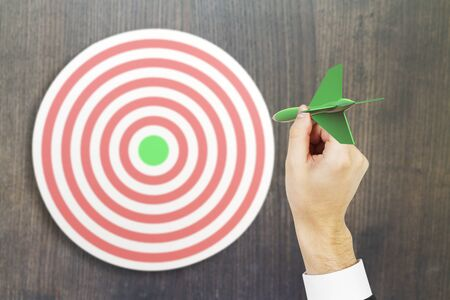 targeting: Targeting concept with businessman hand playing darts on wooden background. 3D Rendering Stock Photo