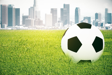footie: Closeup of football on grass. City background. 3D Rendering Stock Photo