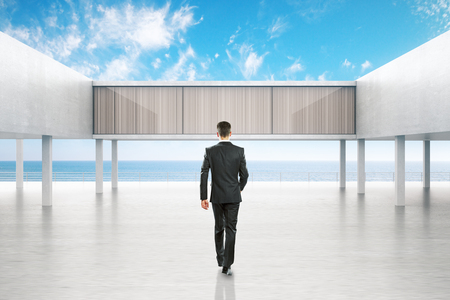 towards: Businessman walking towards concrete exterior by the sea on bright blue sky background. 3D Rendering