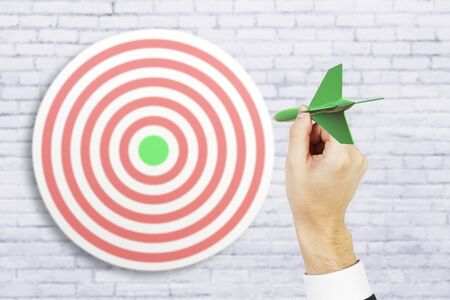 targeting: Targeting concept with businessman hand playing darts on white brick background. 3D Rendering